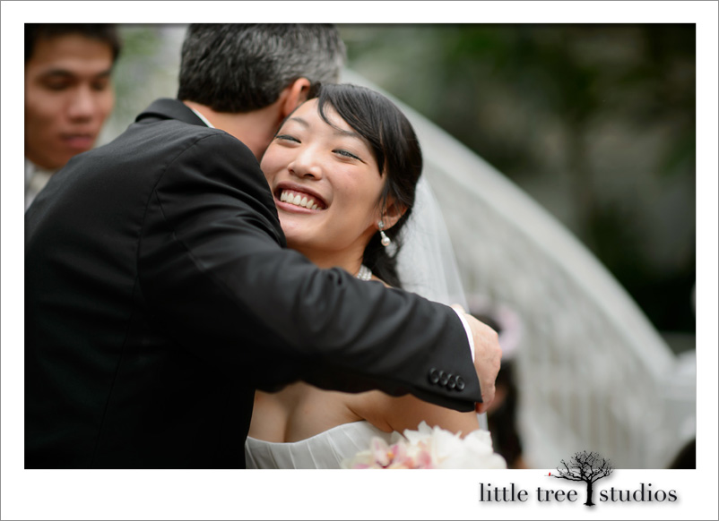 Happy bride hugs wedding officiant, Damian King, at Franklin Park Conservatory in Columbus Ohio