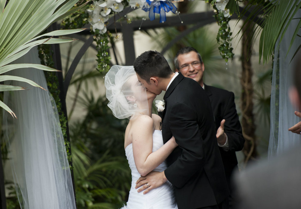 Wedding officiant Damian King smiles as bride & groom kiss in Palm House