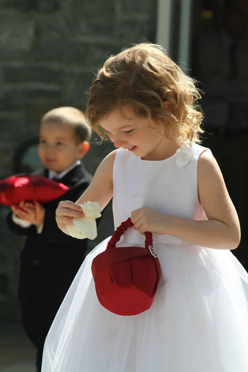 Fascinated flower girl enjoys Kendra and Nathan's wedding in Columbus Ohio while officiant Damian awaits bride's entrance