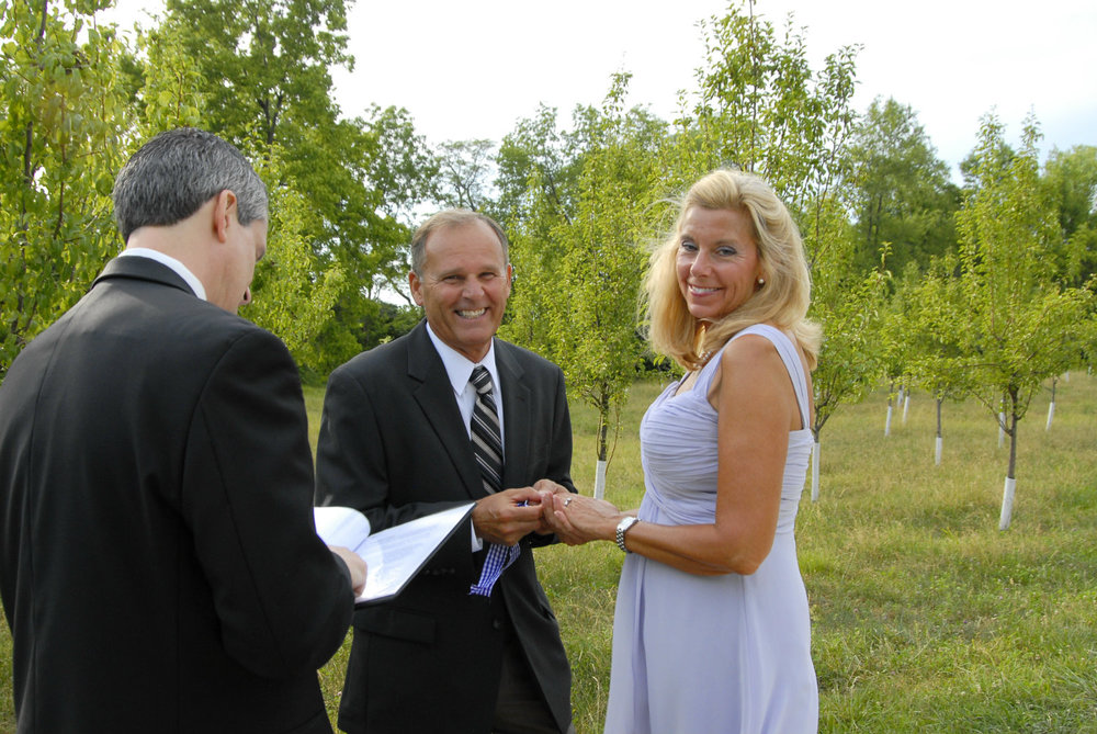Bride and groom laugh with wedding officiant near Columbus Ohio