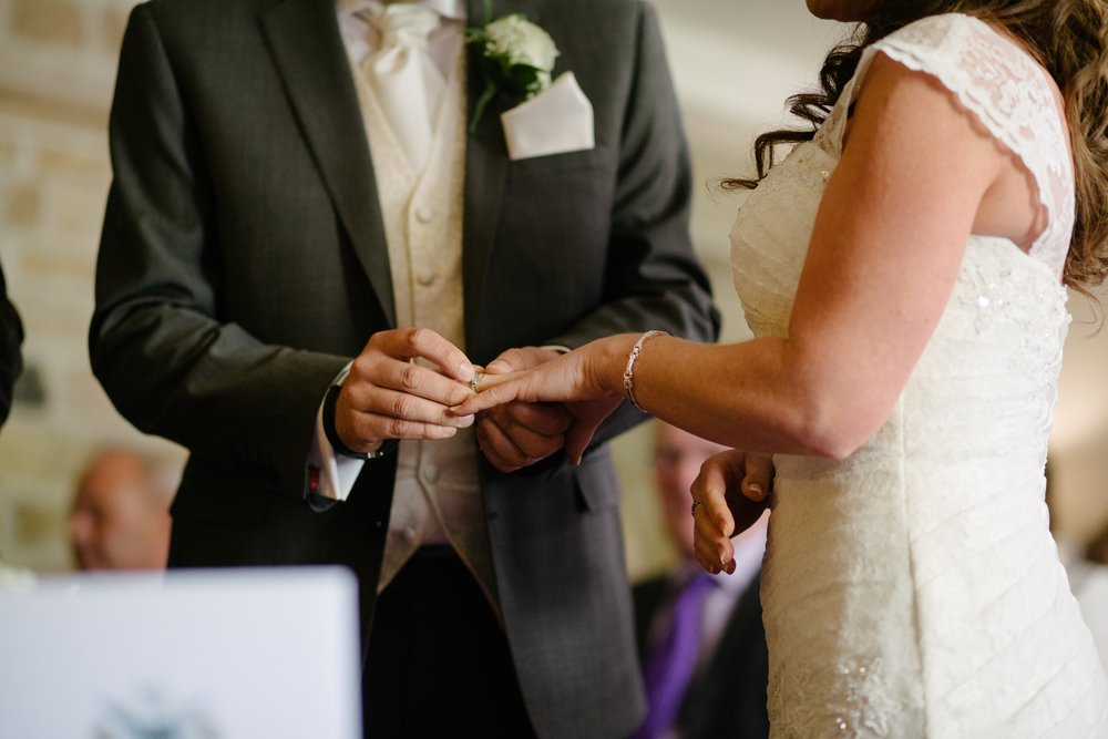 groom puts ring on bride's finger columbus, ohio wedding officiant