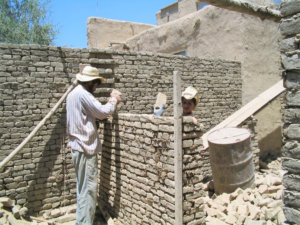 Mari's son helping the mason build the new shelter