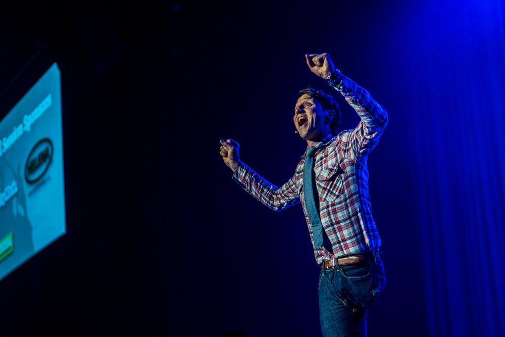 Josh raises his hands in the air during a motivational keynote speech
