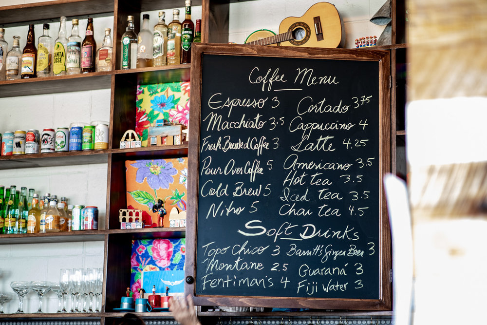 The coffee, tea, and soft drink menu at Buteco. Note the artwork to the left and the  cavaquinho , a small Portuguese string instrument, at the top.
