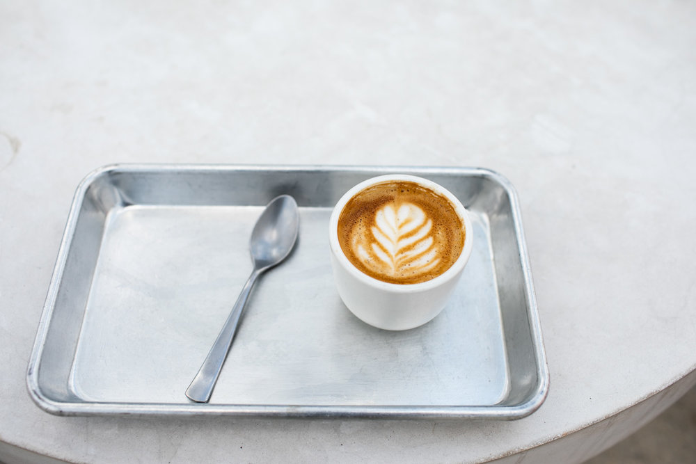 A well-presented cappuccino on a tray.