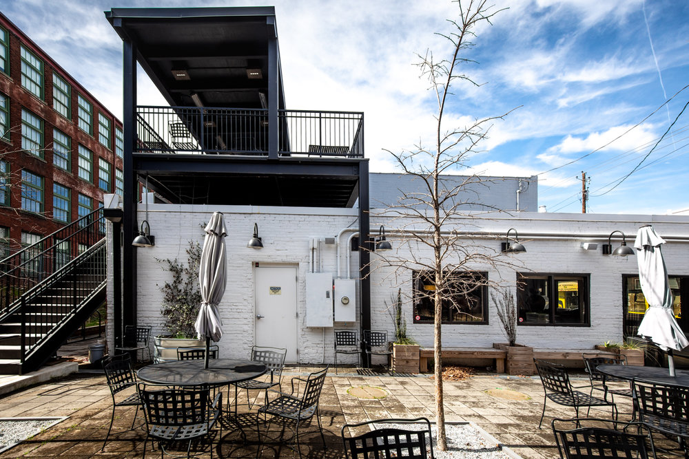 A view of the courtyard at Docent Coffee. There is plenty of outdoor seating and the space is pet-friendly! Note the stairs on the left leading to the second-floor patio with a covered roof.