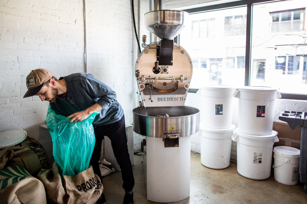 Nolan getting ready to put some coffee beans sourced from Brazil into the hopper for roasting.