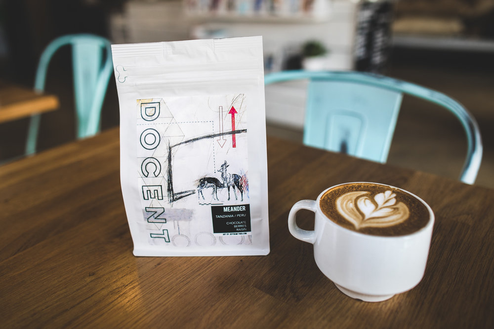 The cappuccino from Docent Coffee, next to the  Meander  triple blend (Tanzania, Peru, Indonesia) coffee bag.