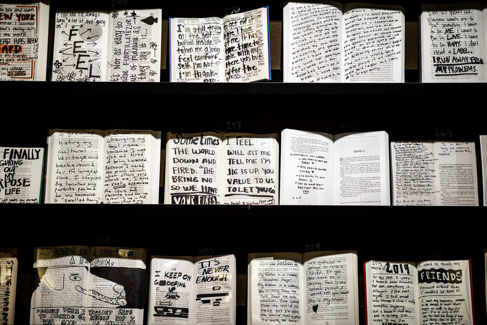 A wider view of books that have been annotated/marked by visitors at Co.Lab's  What Is Your Story  installation. You can respond to the questions/prompts by sending a postcard to the author of the story/question/prompt.