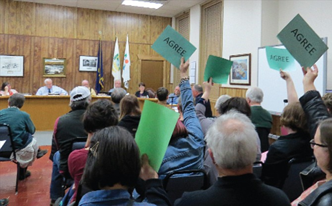 "Audience members use signs reading ""Agree"" or ""Disagree"" to signal their response without being disruptive during an open hearing at The Dalles City Council Monday night. About 70 people were in attendance to hear complaints of misconduct levelled against Councilor Darcy Long-Curtiss."