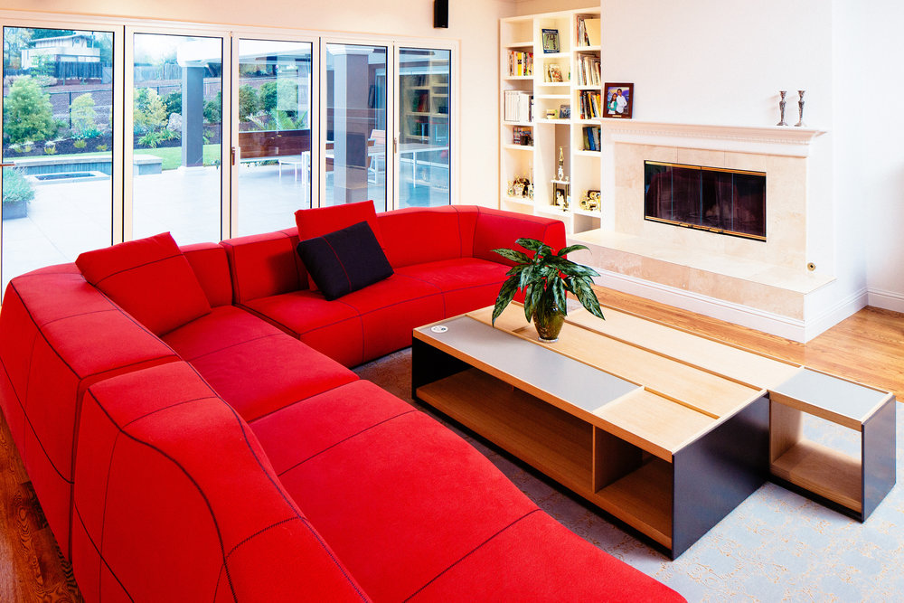 A red corner sofa and a coffee table by B&B Italia