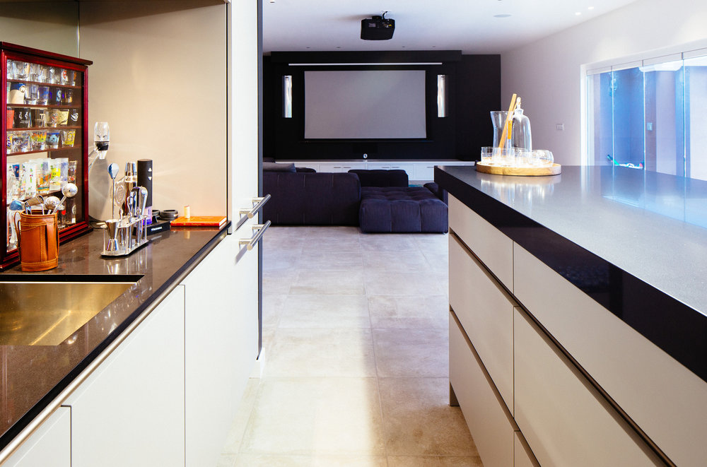 Grey kitchen cabinets, black countertop and a big screen on the back