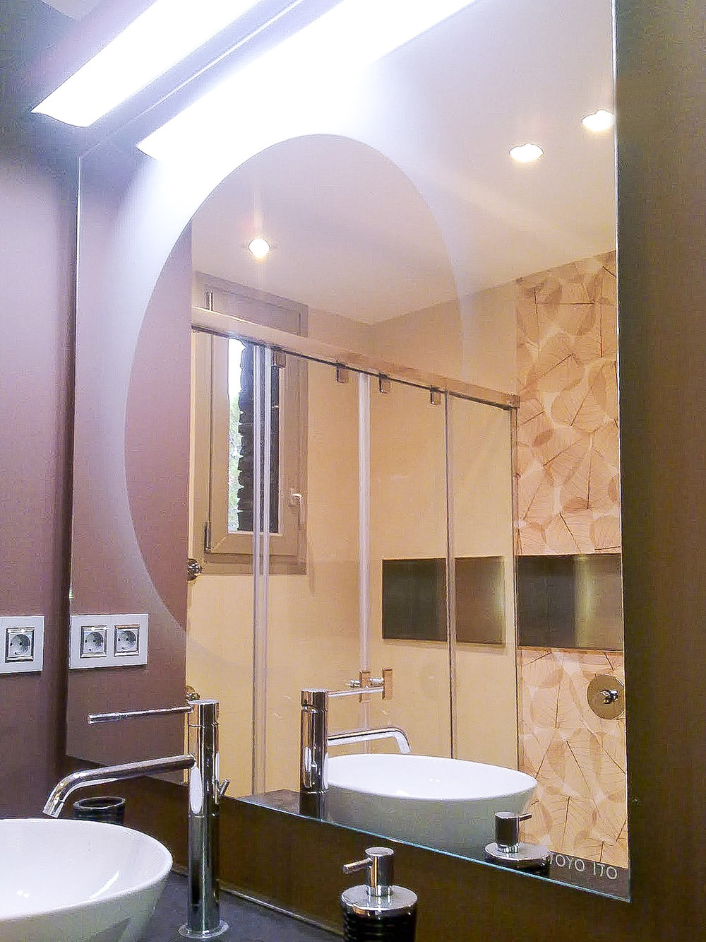 modern bathroom mirror with a wall-sconce on top