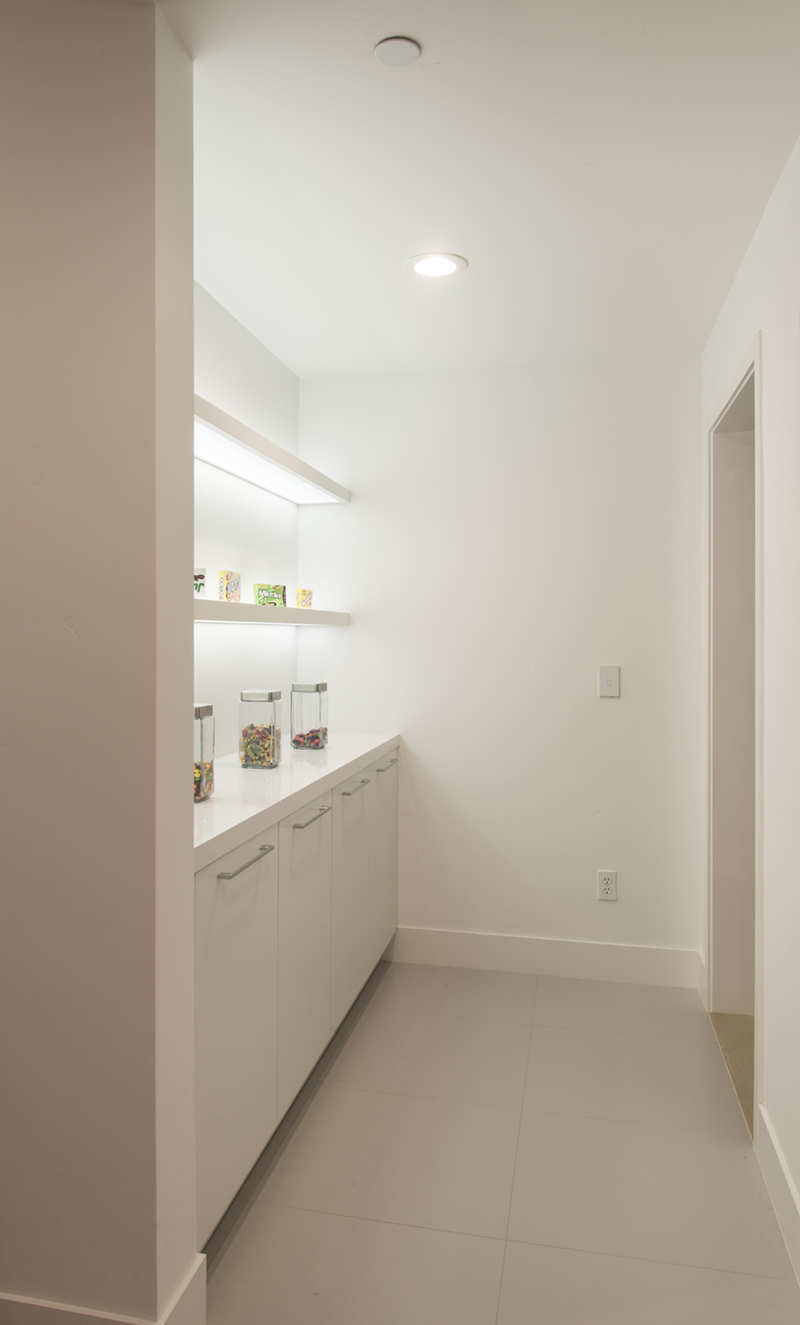 hallway with a white cabinet with shelves with light
