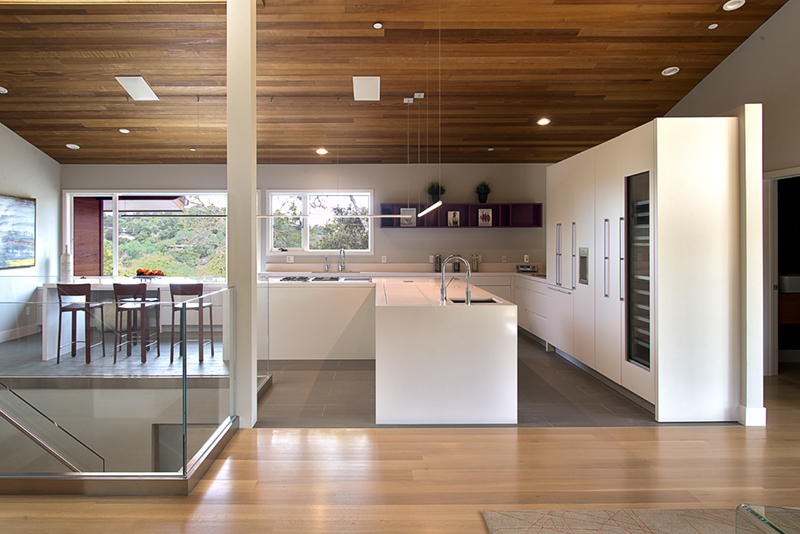 white kitchen with an island and a wood sloped ceiling