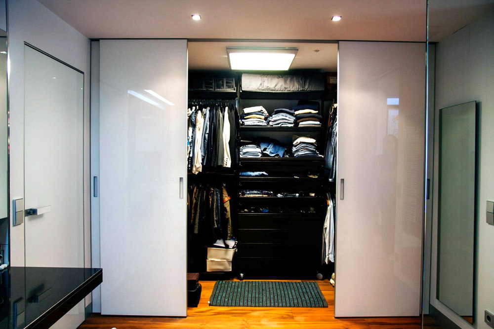 walk in closet with white sliding doors