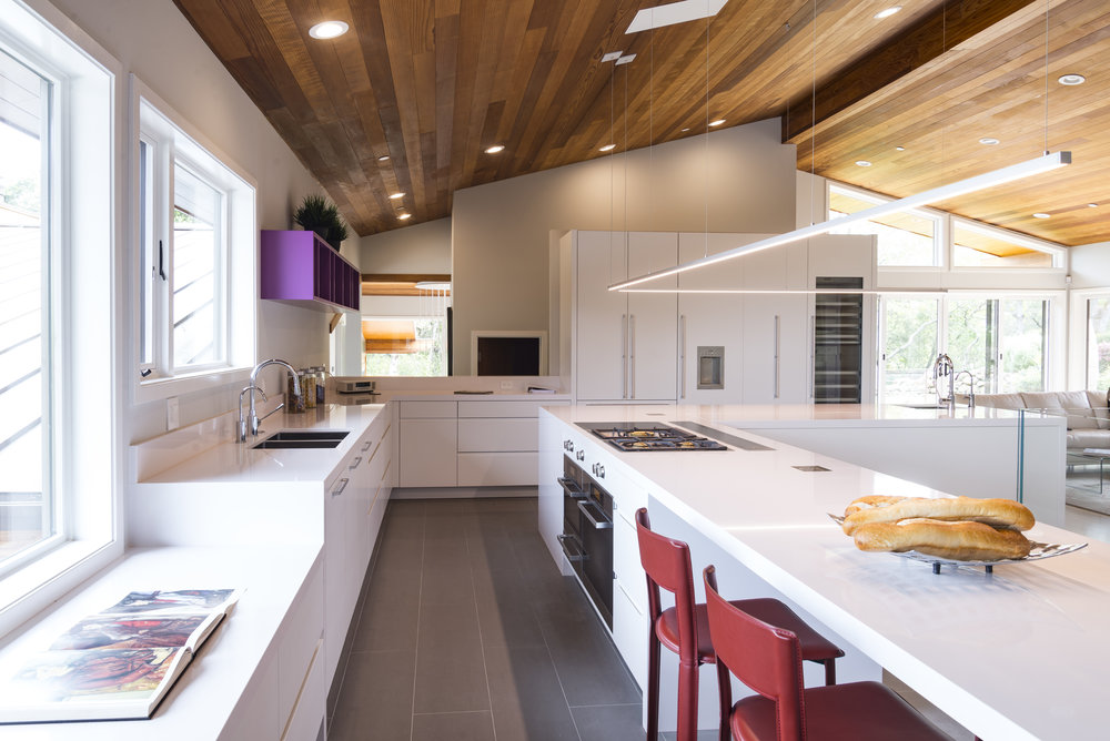 A white kitchen with vaulted wood ceiling.