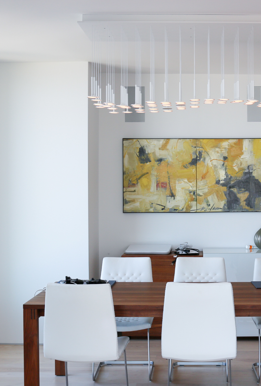 Walnut table by Team 7 and white leather chairs by Desede. Yellow abstract painting and Led Blackbody lamp.