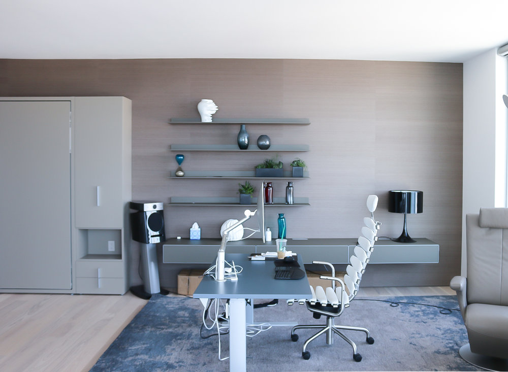 Taupe murphy bed, floating cabinet, glass desk table and a leather office chair.