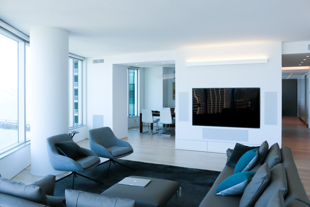 Tv recessed on white wall with speakers in a white living room