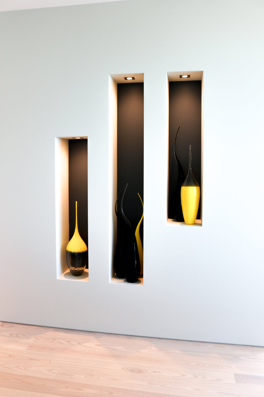 White wall with three niches and three yellow glass vases