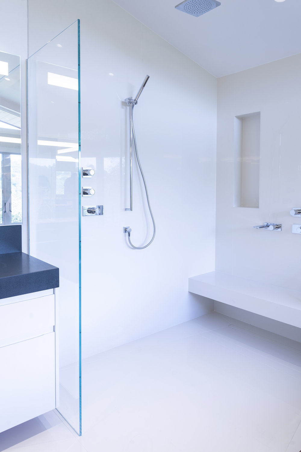 white bathrooms shower with a floating bench