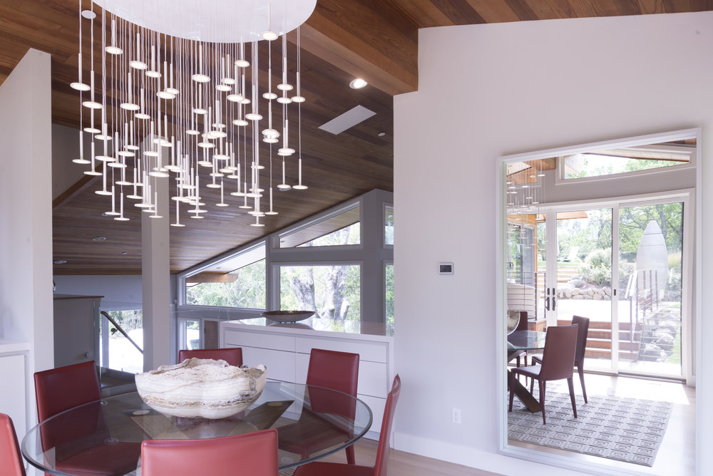 dining room with a big wall mirror and a pendant lamp very modern