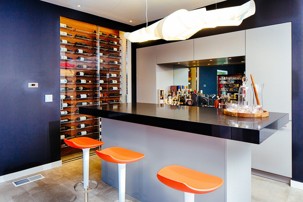 Bar area in ENTERTAINMENT center featuring a built in wine-cellar and custom designed cabinets.