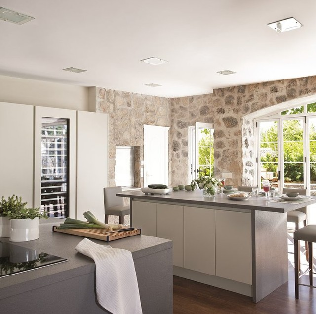 modern kitchen with two islands and a rustic stone wall