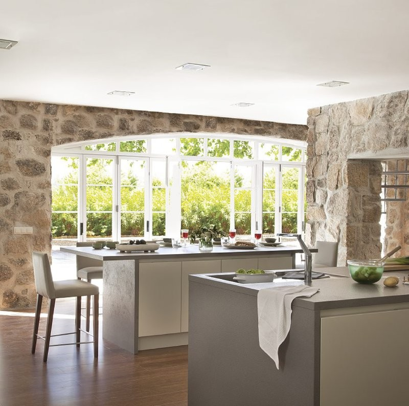 modern kitchen with two islands and a rustic stone wall with a big arched window