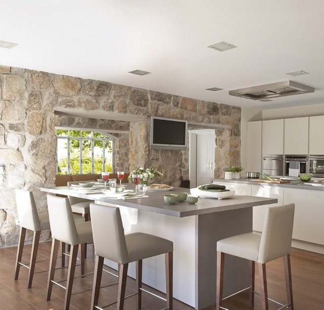modern kitchen with a rustic stone wall and an island with barstools