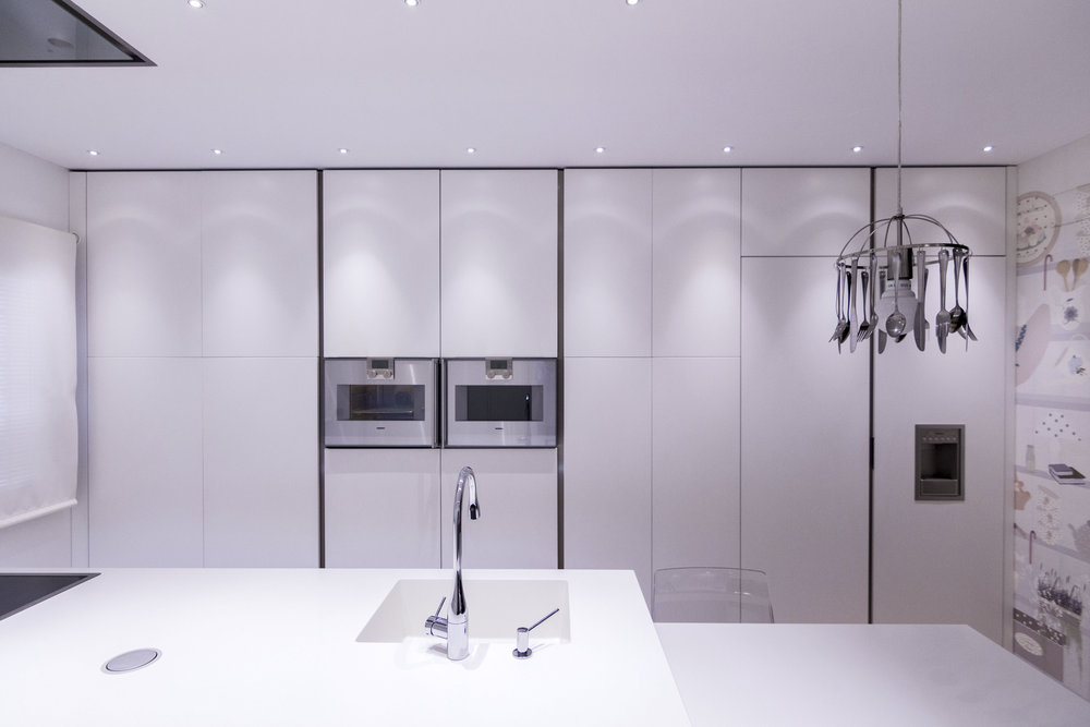 White kitchen with modern cabinets, two ovens and a pendant lamp.