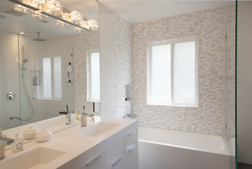 Bathroom vanity with two sinks and a white modern bathtub