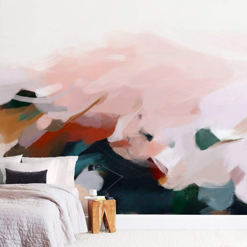 bed in front of a watercolor like wallpaper