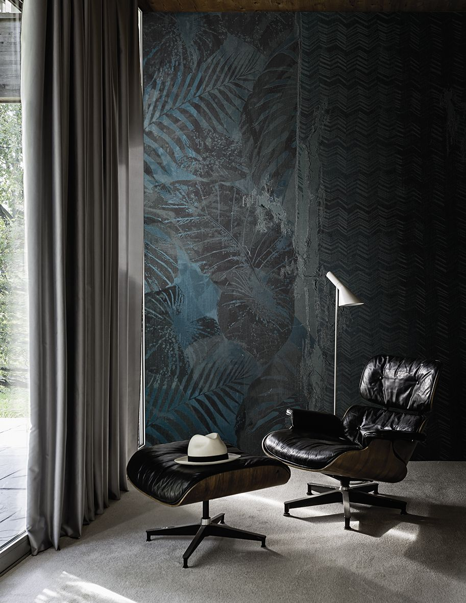 Blue and gray leafs on a wallpaper with a modern chair