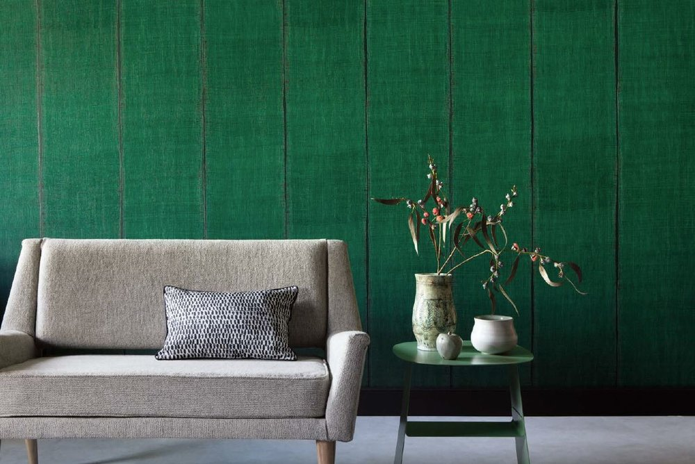Green wallpaper with lines and a sofa