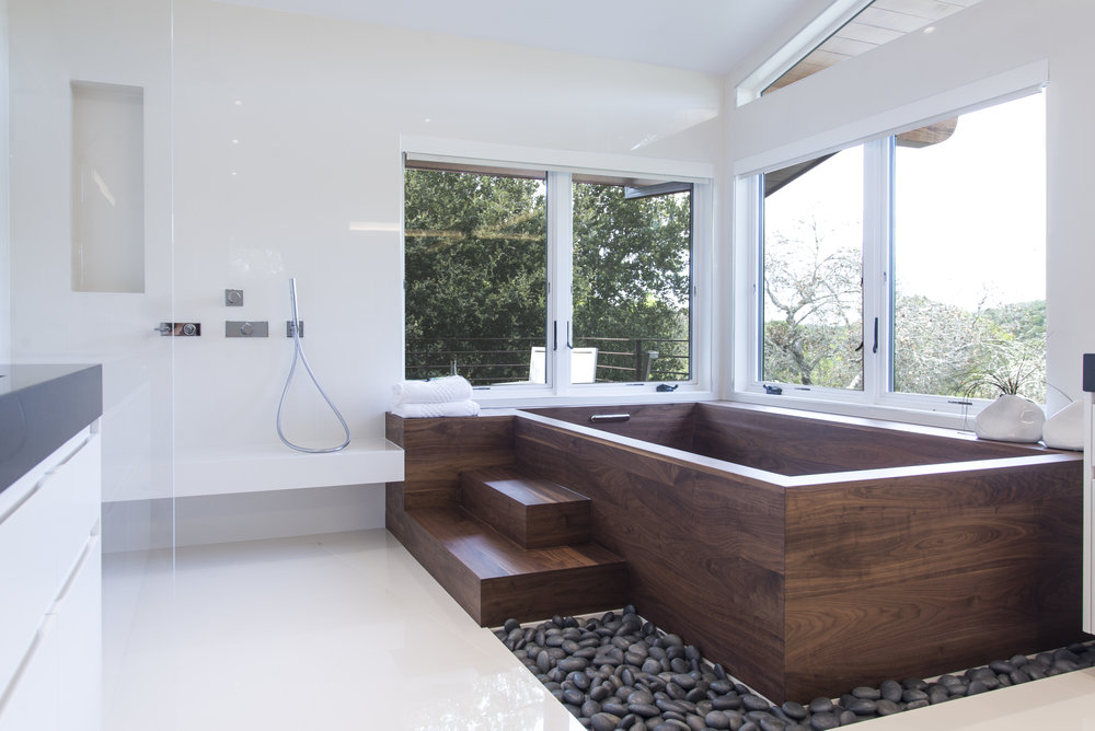 wood bathtub and a white shower