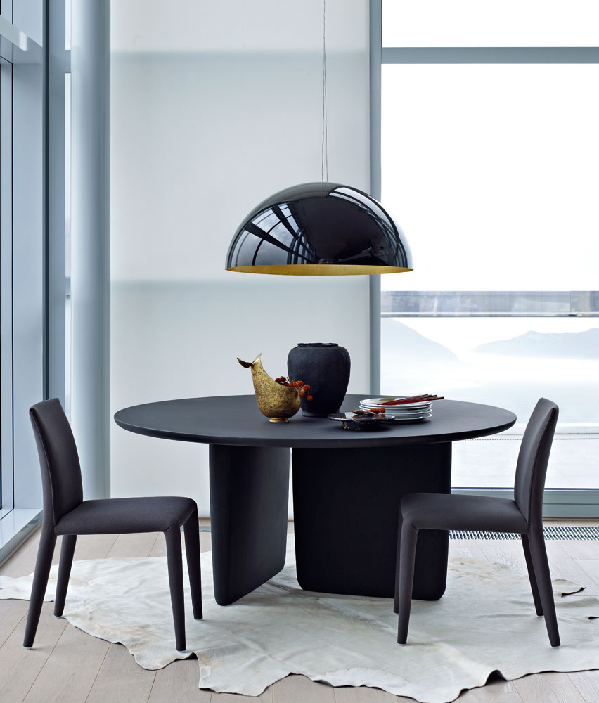 black round dining table with two chairs and a lamp in front of a window