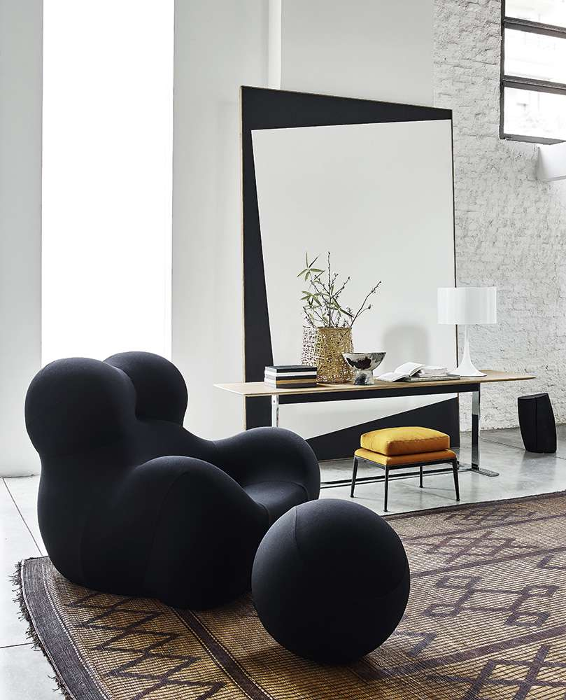 A black chair with a footrest in a black room
