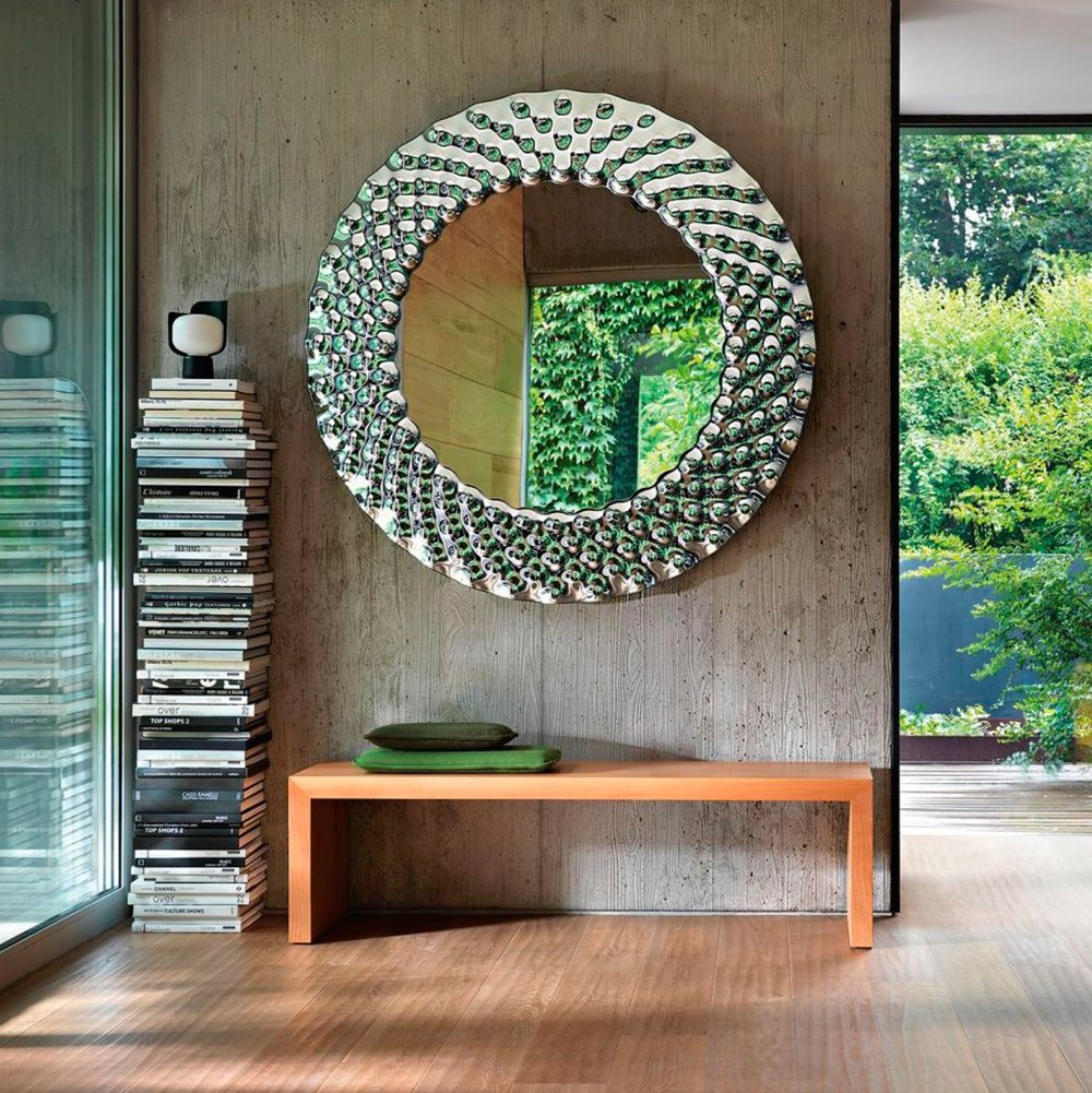 a big round mirror in a wall over a bench