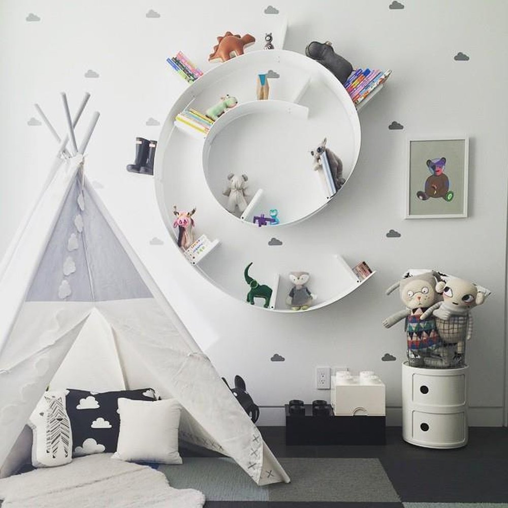 white kid room with a round bookshelf in the wall