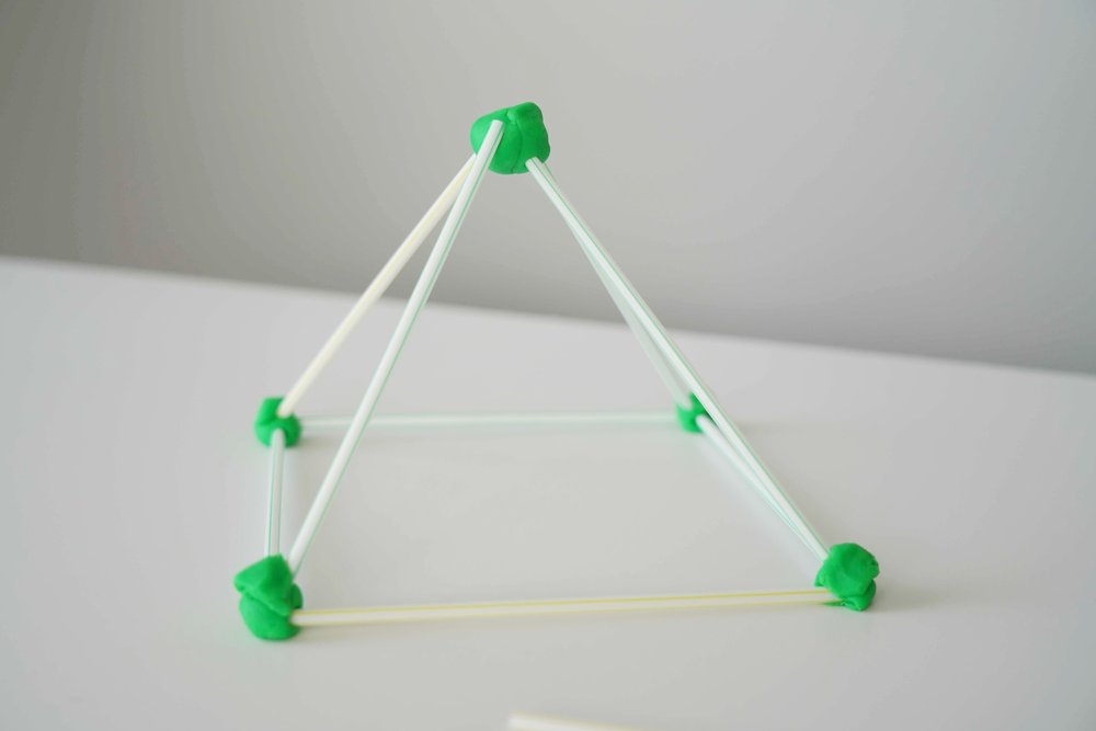 A pyramid built with straws and clay.