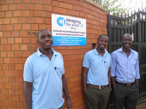 Bottom From left: Picho, Alan, and Collins stand proudly in front of the new Imaging the World Sign.