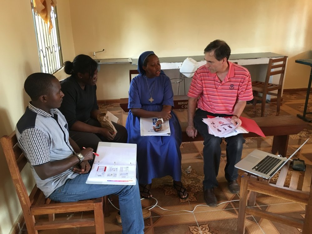 Dr. Craig Sable discusses the project plan with Moses, Henrietor, and Sister Angela.