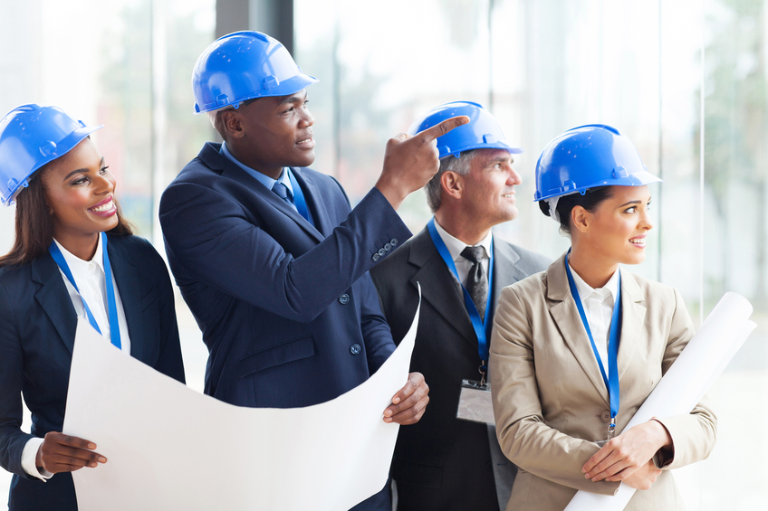 diverse-group-in-hard-hats-discussing-building-pla.jpg