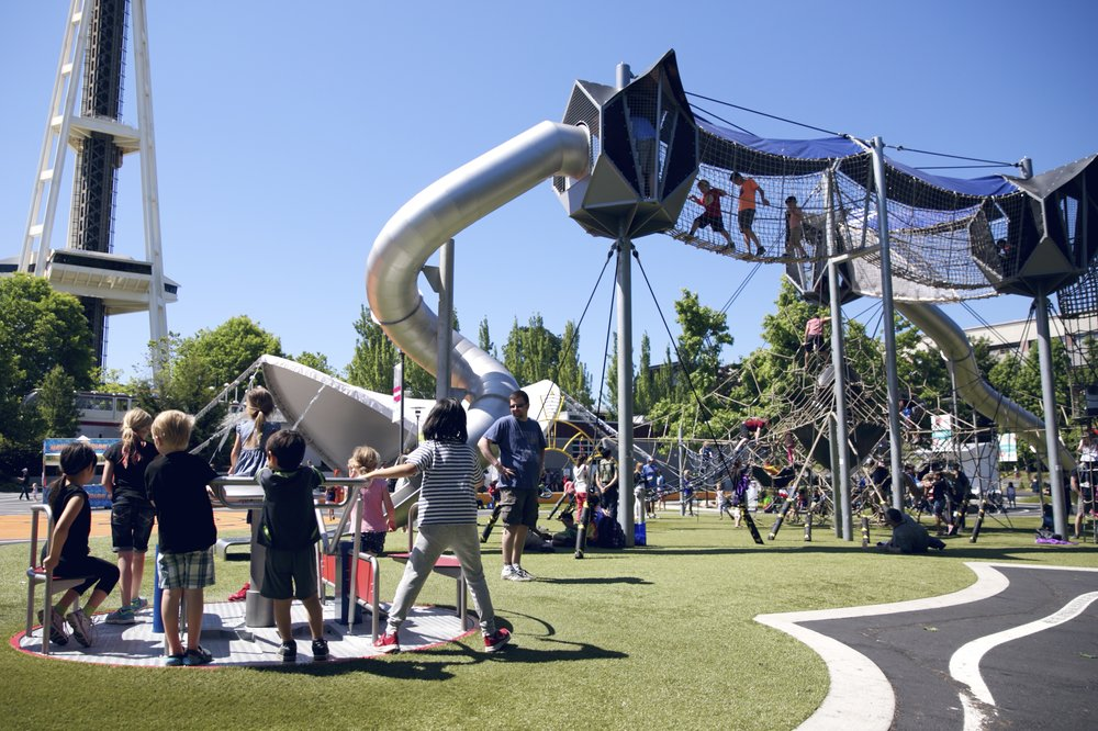 Image description: A group of kids play on a merry-go-round in the foreground of a play park adjacent to Seattle's Space Needle. A play structure with slides and a net bridge is in the background.