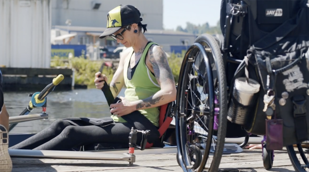[Image description: A rower from Seize the Oar is setting up to practice on Lake Washington in Renton, Washington. She is wearing black tights and a lime green top. She is wearing dark rimmed glasses, and her hair is in a ponytail, tucked inside of the green and black baseball cap. She has multiple tattoos across both of her arms and has small gauges in her ears. She is slightly smiling as she puts on the boat's safety straps.] - Courtesy of Teal Sherer/Seize the Oar