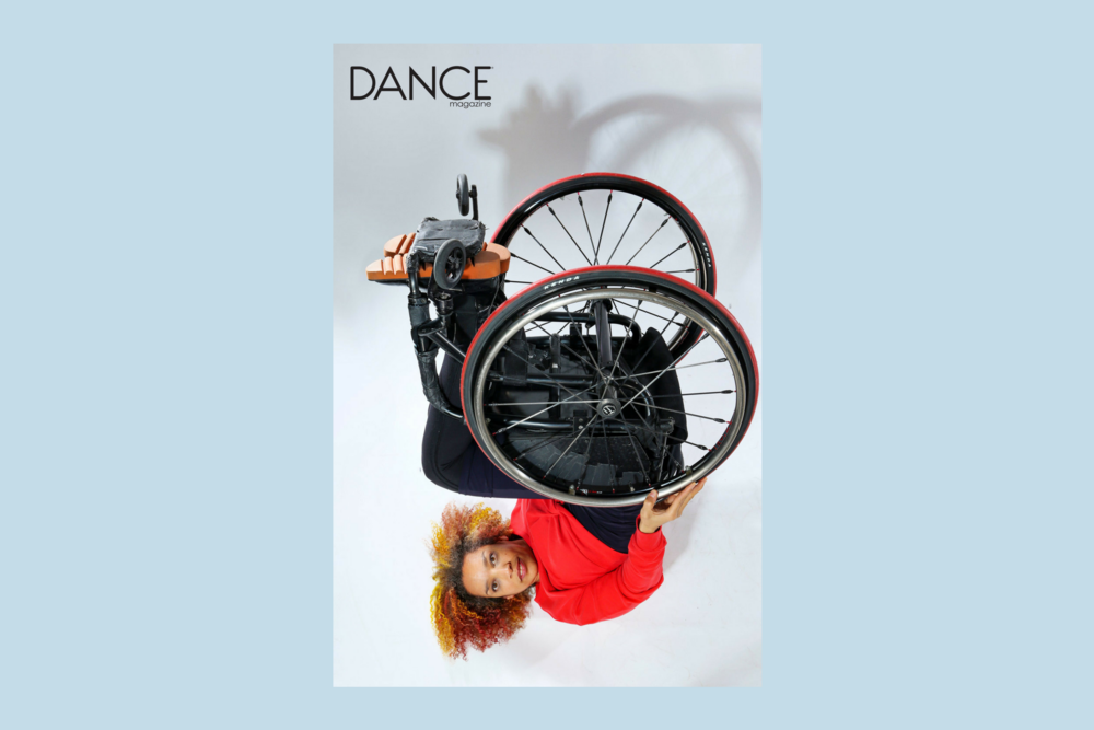 [Image description: Dancer Alice Sheppard poses while resting on her back, with her legs and wheelchair extended in the air above her torso. She is wearing a red, long-sleeved top and black pants.]