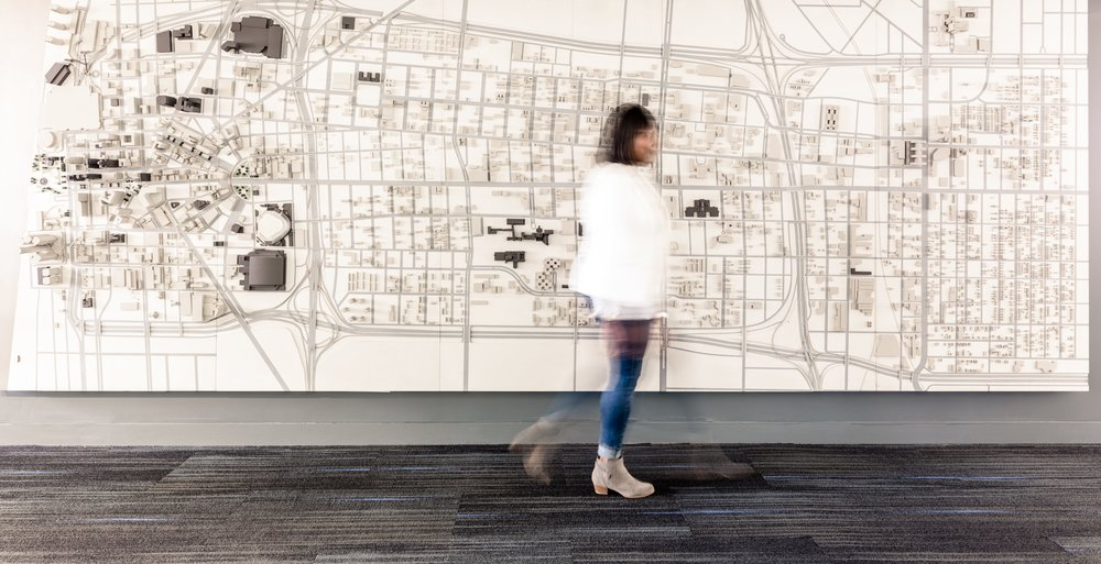 [Image description: Tiffany Brown, wearing a white jacket, skinny jeans, and boots, walks by a mural-size map of Detroit. The image is a composite that shows Tiffany in motion. Photo credit: Paul Anderson, hunker.com]