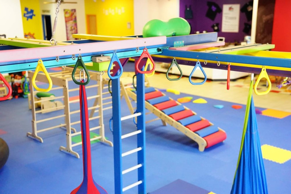 [Image description: An interior shot of Bravery Kids Gym. The room is filled with play equipment, with ladders, rings, and swings, in primary colors. The floor is covered with blue mat tiles.]